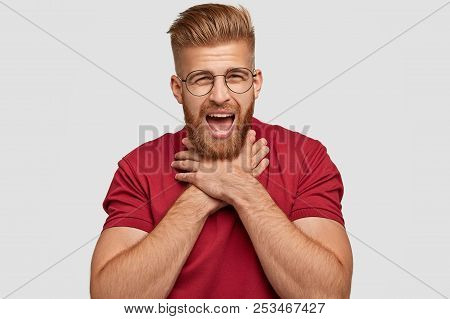 Photo Of Tired Bearded Male With Negative Facial Expression, Suffers From Suffocation, Keeps Hands O