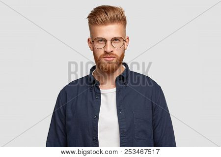 Indoor Shot Of Serious Redhead Youngster Has Thick Ginger Beard, Mustache, Looks Confidently At Came