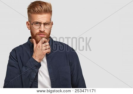 Studio Shot Of Brutal Serious Ginger Male With Thick Beard, Holds Chin, Raises Eyebrows, Being Deep
