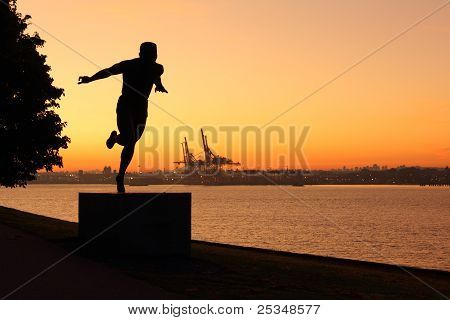 The silhouette of a statue of an athlete crossing the finish line beside the Stanley Park seawall at dawn. Burrard Inlet and Vancouver Harbor are in the background. British Columbia, Canada. poster
