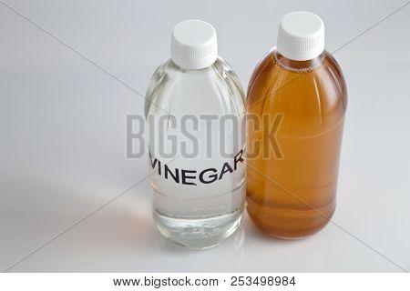 white vinegar and apple cider vinegar on white background