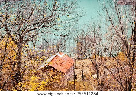 Old house near lake, surrounded by autumn trees, hunting lodge in forest, a place of solitude, communing with nature. Top view. poster