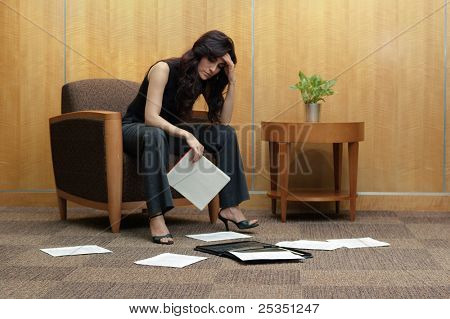 Frustrated business women in office lobby, with paper mess.
