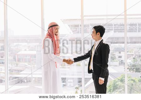Arab Business Partners With Asian Partners After A Successful Business Deal.two Businessman Shake Ha