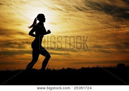 Beautiful young woman running in front of a sunset.