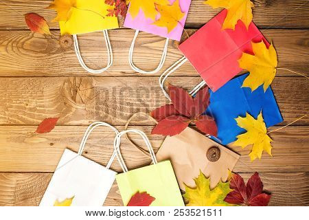 Color Shopping Paper Bags And Autumn Leaves, Flat Lay, Copy Space. Autumn Shopping, Sales Concept. A
