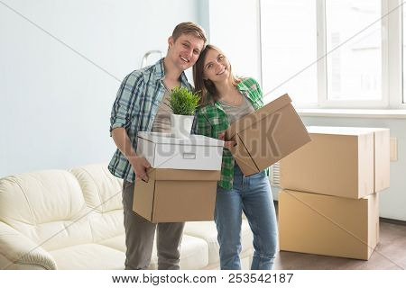 Home, People, Moving And Real Estate Concept - Happy Couple Having Fun And Riding In Cardboard Boxes