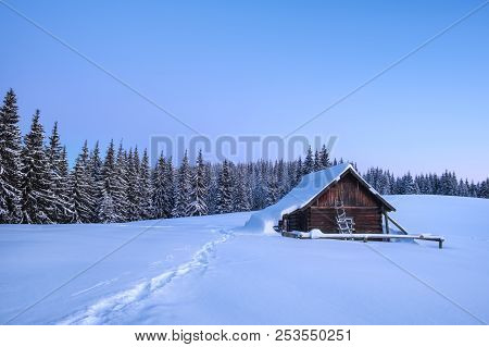 Winter Landscape Of A Mountain Forest With A Cabin At Sunrise. Trail Stamped In The Snow Towards The