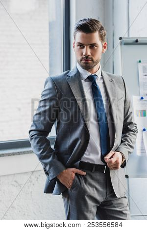 Handsome Serious Young Businessman In Suit Standing With Hand In Pocket In Office