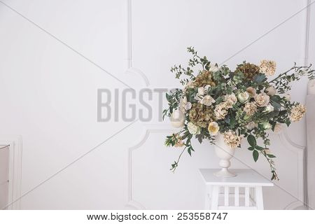 Home Interior Decor, Bouquet Of Lilacs In A Vase And Books On Rustic Wooden Table, On A White Wall B