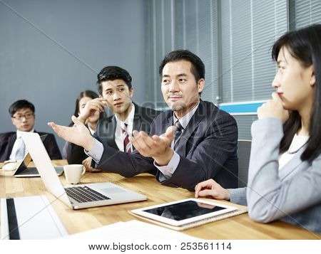 Asian Corporate Executive And His Business Team Meeting And Negotiating With Client.