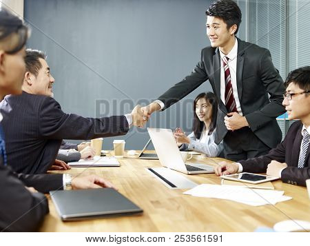 Two Asian Corporate Executives Shaking Hands Over Negotiation Table.