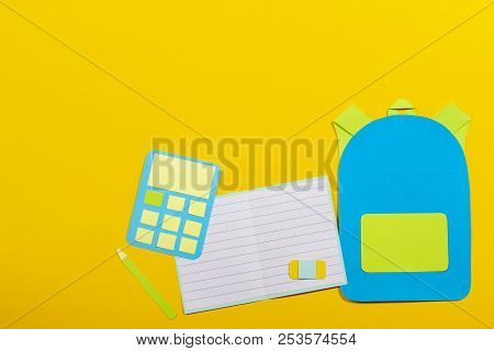 School education papercut background. School bag backpack, notebooks and calculator paper cut on yellow background poster