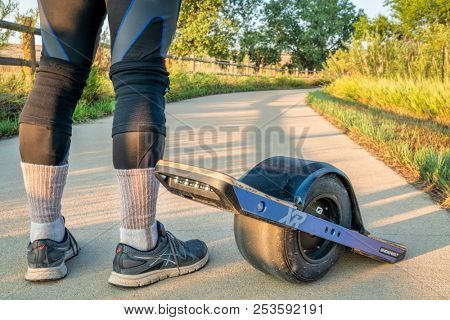 Windsor, CO, USA - August 4, 2018:  Preparing to ride the onewheel electric skateboard on the Poudre River Trail in northern Colorado.