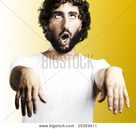 young man imitating a zombie against a yellow background