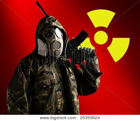 portrait of soldier with rifle and gas mask with radioactive symbol as a background