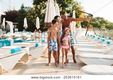 Photo of idyllic family with children resting near luxury swimming pool with white fashion deckchairs and umbrellas during travel or spa resort