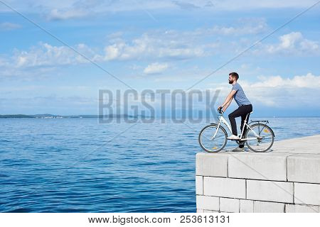 Young Bearded Man Tourist On Bicycle On High Paved Stone Sidewalk Enjoying Clear Blue Sea Water. Act