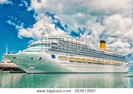 Big Cruise Ship. Large Luxury Cruise Ship On Sea Water And Cloudy Sky Background Docked At Port Of S