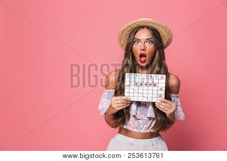 Portrait of disappointed outraged woman 20s wearing straw hat holding period calendar isolated over pink background in studio poster