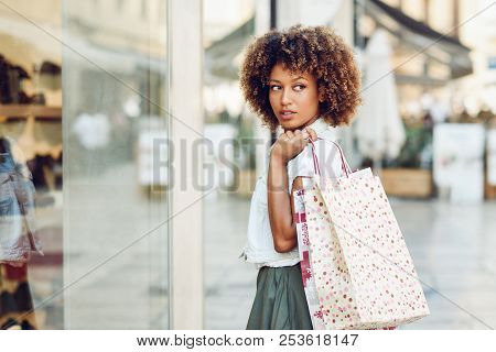 Young Black Woman In Front Of A Shop Window In A Shopping Street. African Girl With Afro Hairstyle W