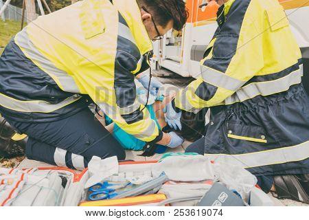 Paramedics performing first aid at ambulance, helping a woman poster
