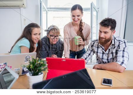 Four co-workers smiling, while watching together a professional business presentation or a funny video on tablet in a modern shared office space for freelancers or young entrepreneurs