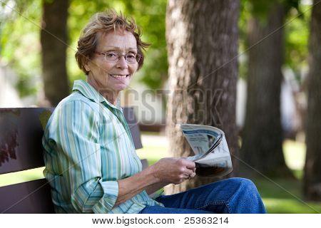 Portrait of smiling elderly woman reading newspaper in park