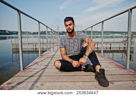Handsome Tall Arabian Beard Man Model At Stripped Shirt Posed Outdoor On Pier Of Lake. Fashionable A