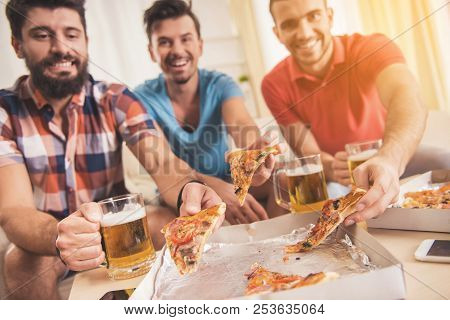 Young Smiling Men Drink Beer And Eat Pizza At Home. Friends On Party. Weekend At Home. Three Happy F