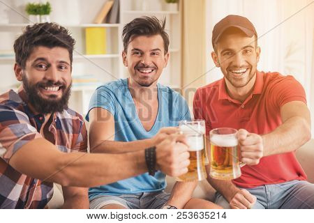 Three Young Men Drinking Beer On Party At Home. Friendship Concepts. Drinking Beer. Smiling Young Ma