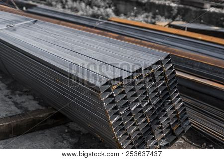 Square Flat-rolled Pipe Metal Profile In Packs At The Warehouse Of Metal Products. Weathered Metals