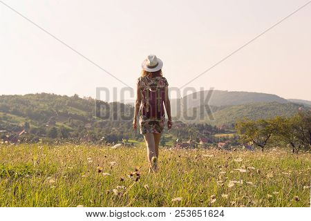 Girl in vacation. Summer vacation. Traveler girl walking through fields. Young girl traveler walking in nature. Traveler with backpack in nature. Girl traveler walk through nature in summer day. Traveler. Summer. Backpack. Girl. Walk. Nature. Vacation. Li