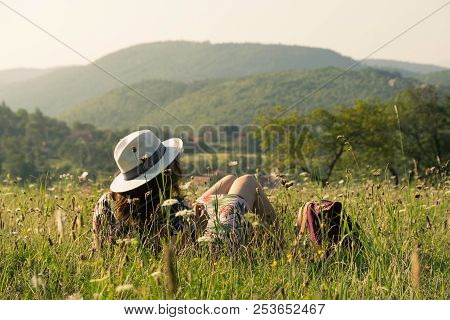 Woman on vacation relaxing in fields. Summer vacation. Young woman traveler in vacation in nature. Traveler in vacation with backpack in nature. Girl traveler relaxes in fields in vacation. Traveler. Vacation . Backpack. Woman. Nature. Healthy lifestyle