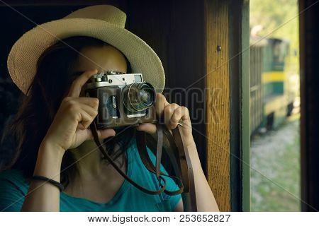 Vintage photo camera. Vintage concept. Traveler girl using vintage camera. Girl traveler taking photo from the train. Hipster woman photographing from train with vintage camera. Girl traveler. Hipster. Train. Vintage