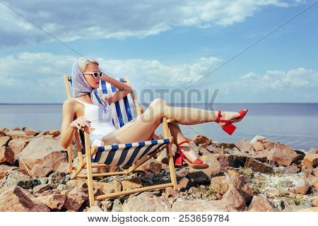 Attractive Elegant Girl In Retro Swimsuit Resting In Beach Chair On Rocky Shore Near The Sea