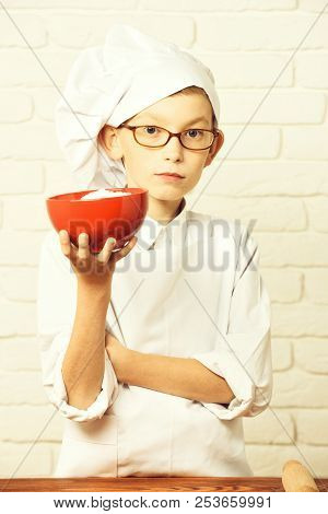 Serious Face With Glasses Standing Near Table And Holding Red Bowl On Brick Wall Background. Serious
