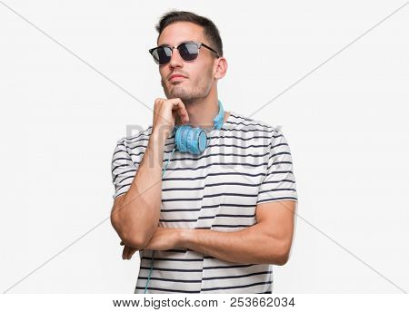 Handsome young man wearing headphones with hand on chin thinking about question, pensive expression. Smiling with thoughtful face. Doubt concept.
