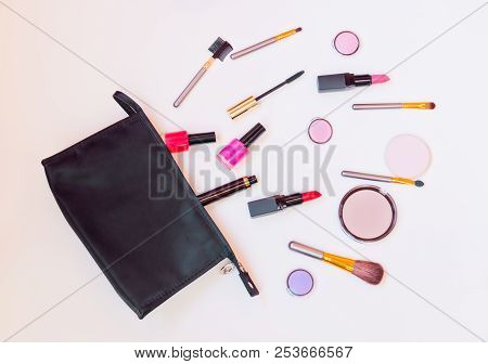 Black Makeup Bag With Cosmetic Beauty Products Spilling Out  To Pastel Colored Surface