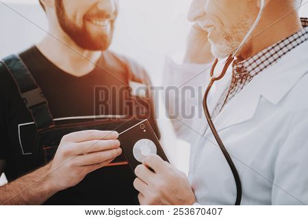 Computer Doctor In White Uniform With Stethoscope. Young Man With Smartphone. Examination Of Didital