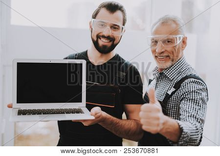 Two Smiling Men With Laptop In Workshop In Repair Shop. Thumbs Up. Computer Hardware. Young And Old