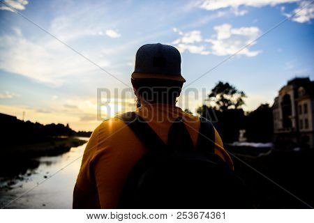 Guy in front of blue sky at evening time admire landscape. Enjoy pleasant moment. Take moment to admire sunset nature beauty. Peace and relax. Man in cap enjoy sunset while stand on bridge poster