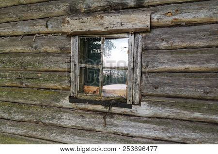 Old Window In The Log Wall Of The House. The Window Is Located In An Old Village Building. Belarus.