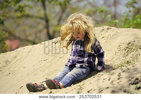 Child Slide From Pile Of Sand On Idyllic Day. Kid Play In Sand In Spring Or Summer Park. Childhood,