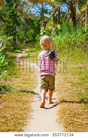 Happy Barefoot Child Walk Alone On Beach By Path, Explore The Jungle. Little Boy Carry Shoes On Stic