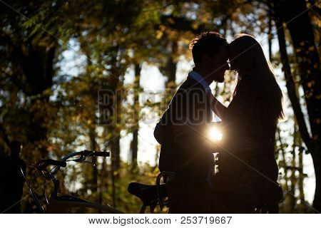 Lit By Setting Sun Profile Silhouettes Of Romantic Couple, Young Man And Attractive Girl Close Toget