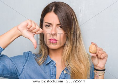 Young adult woman over grey grunge wall showing dried walnut with angry face, negative sign showing dislike with thumbs down, rejection concept poster