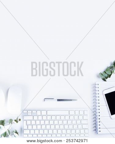 Flat Lay Home Office Workspace With White Modern Keyboard, Notebook And Silver Green Eucaliptus Twig