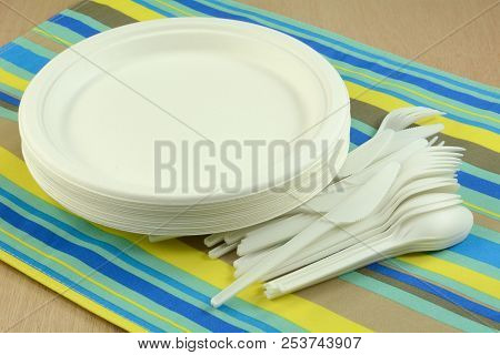 White Eco-friendly Disposable Compostable Plates And Cutlery Made From Sugar Cane Fiber On Place Mat