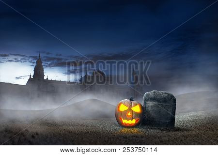 Glowing Halloween Pumpkin Beside Grave Stones With Old Building Background. Halloween Background